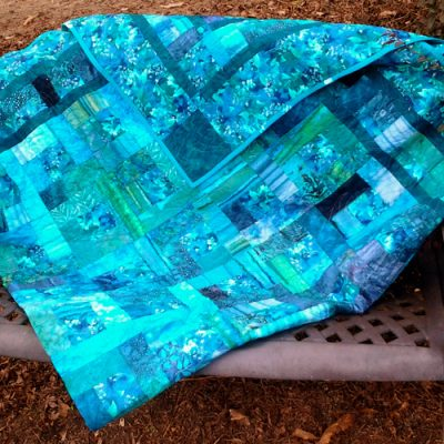 Photo of stash blue block quilt draped over bench