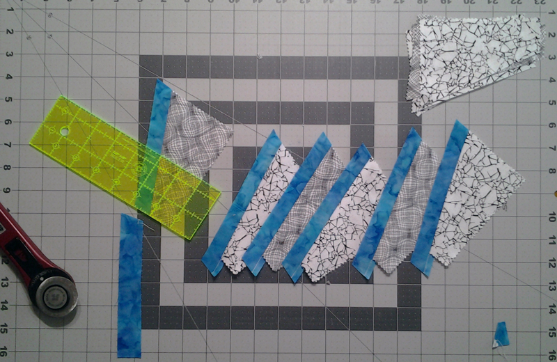 Photo First side of Black & White fabric pieces sewn to contrast strip, pressed and trimmed on one end with ruler