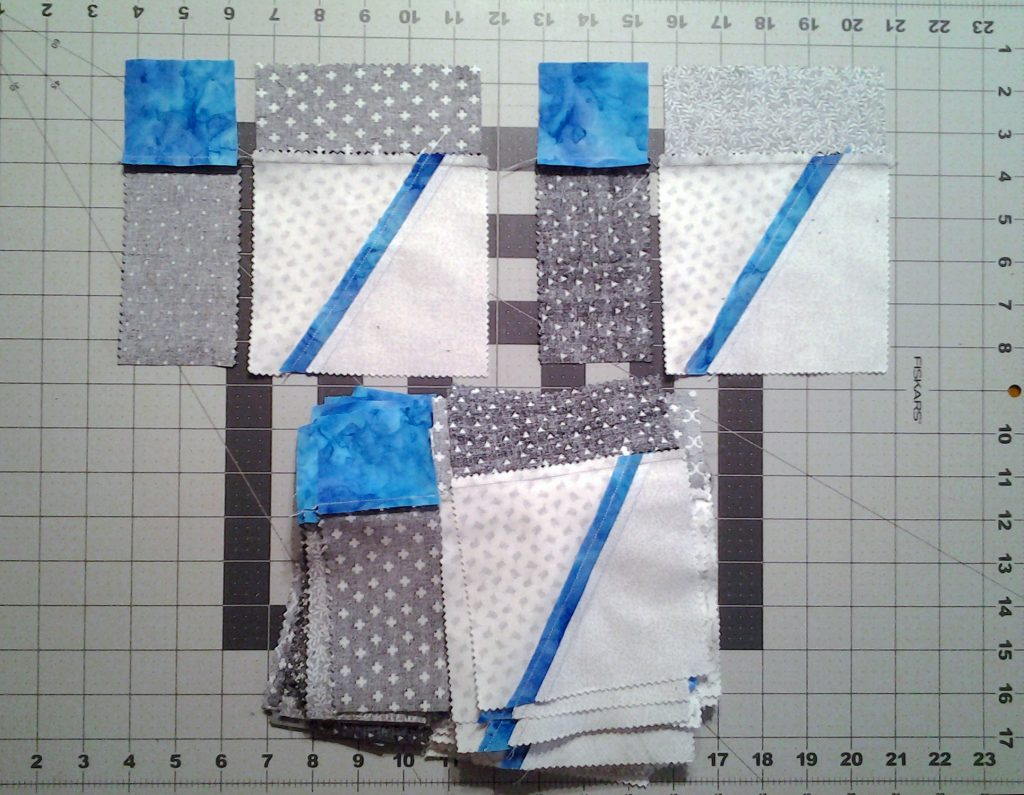 Photo Modern Improv Black White & Turquoise Quilt Block Pieces after first assembly step indicating beginning of 2nd step