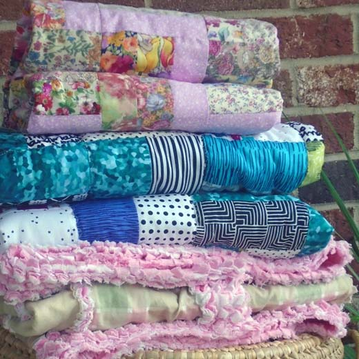 Photo of a stack of folded baby quilts show how to spray baste your quilt with temporary spray adhesive