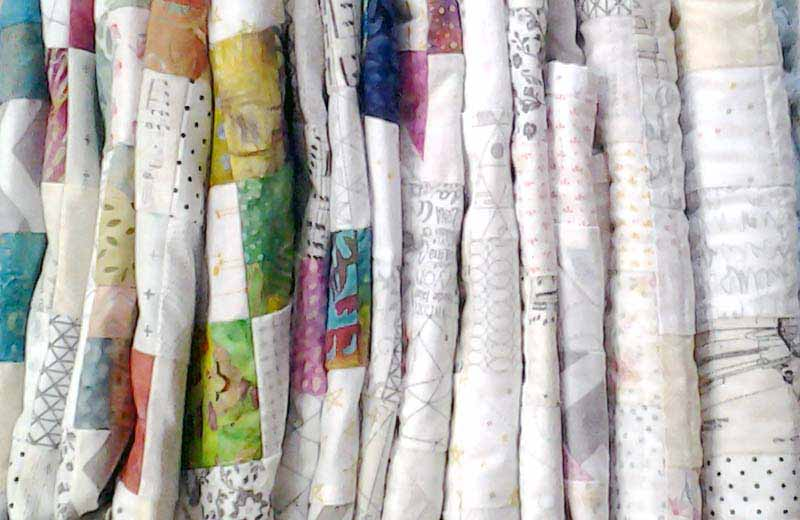 photo of an assortment of folded Low Volume Quilts
