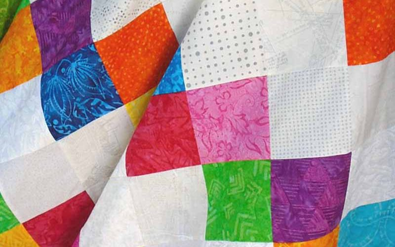 photo of Batik-Low Volume Charm Square Baby Quilt