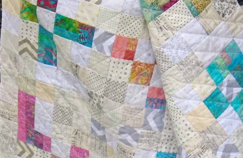 photo of Low Volume Patchwork Quilt with Bright Batiks