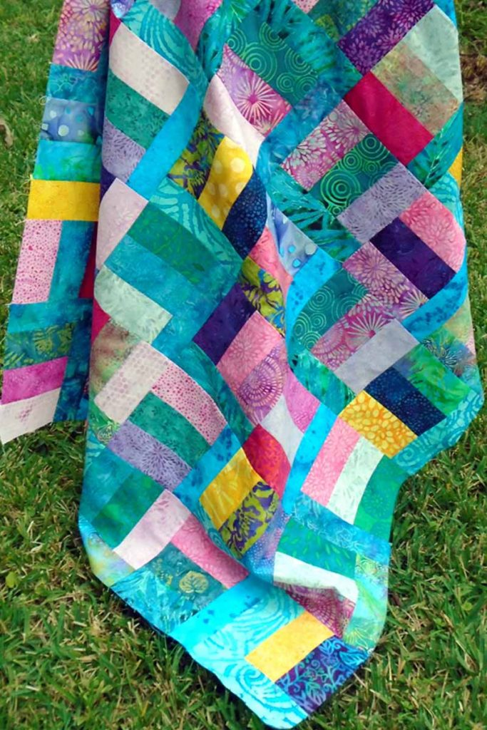 photo of Asymmetrical Batik Charms Rail Fence Quilt