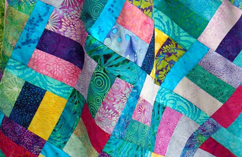 photo of Asymmetrical Turquoise Batik Charms Rail Fence Quilt