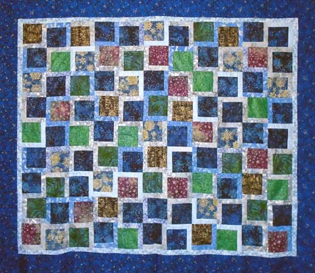photo of completed batik charm square holiday quilt
