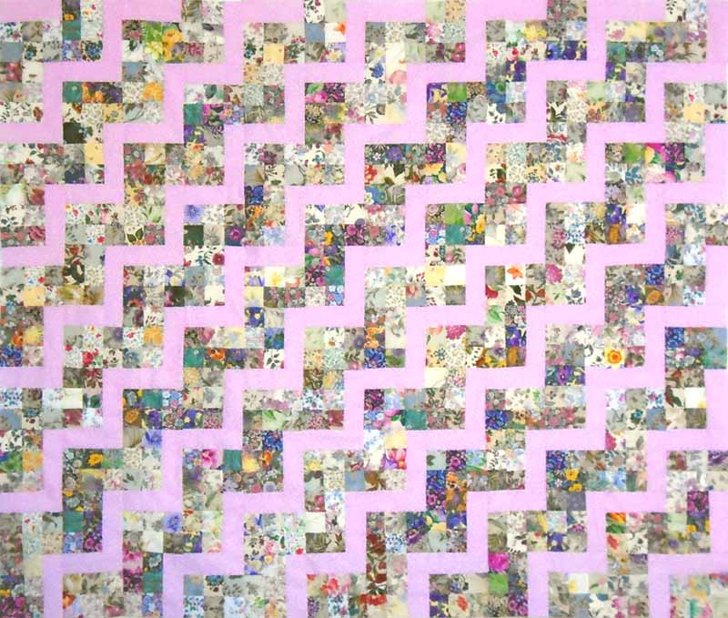 image of pink patchwork rail fence lap quilt