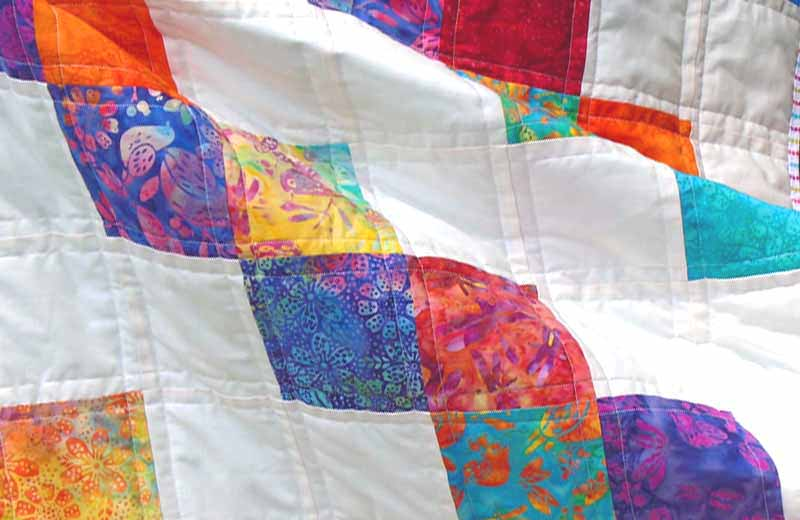 image of Batik Charm Square Brick Path Baby Quilt with Free Pattern