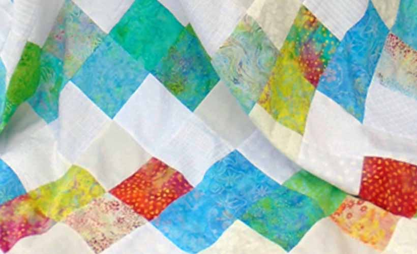 image of batik and low volume charm square quilt